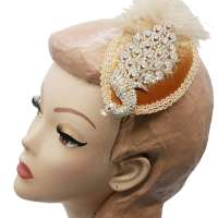 Fascinator with decorative peacock, rhinestones and feather in gold